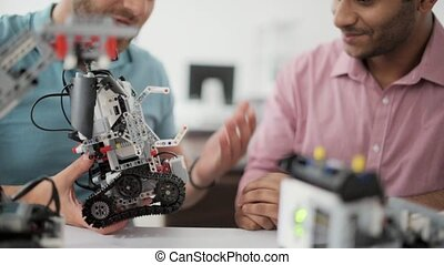 Young man showing new robotic device to colleague - Check it...