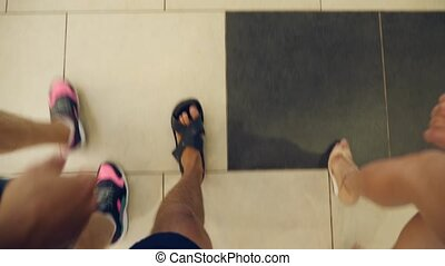 Three people walk on the tile floor .. two men and one woman...