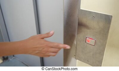 Press the elevator button. The female hand presses the...