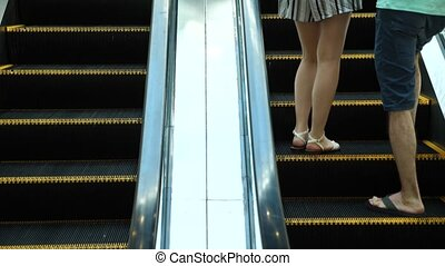 Moving steps of the escalator. People move on an escalator, Slow motion.