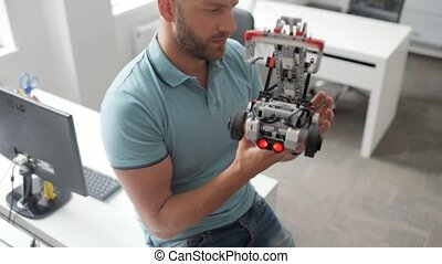 Focused young man elaborating robot at work - The best...