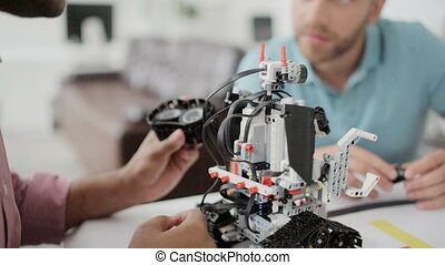 Millennial colleagues chatting over self automated robot -...