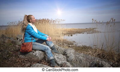 The young woman sits on stones on the bank of the gulf and...