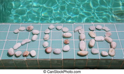 Date 2018 is laid out by pebble stones on the edge of the pool in the tropical resort
