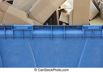 Blue recycling container for paper with cardboard boxes....