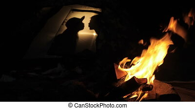 Silhouette of a kissing couple in tent near fire