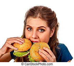 Woman eating two hamburgers. Girl bite of very big burger