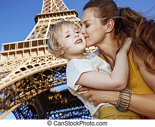 happy mother and child tourists kissing against Eiffel tower...