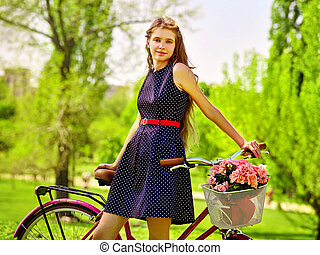 Girl wearing blue polka dots sundress rides bicycle with...