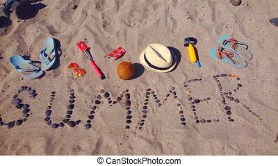 Word summer from sea stones laid out on sand on the beach....