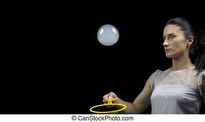 Young woman making smoky soap bubble on black background