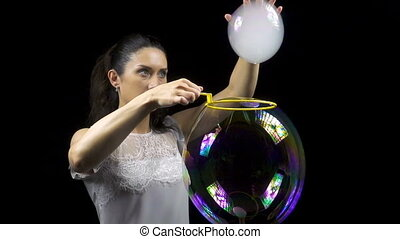 Attractive woman making smoky soap bubble on black...