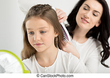 Smiling mother combing hair of cute little daughter looking...