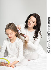 Smiling mother combing hair of cute little daughter with...