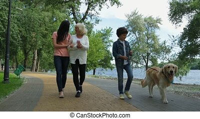 Little boy walking with his family and dog