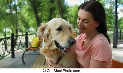 Beautiful woman sitting on the bench with her dog - Enjoy...