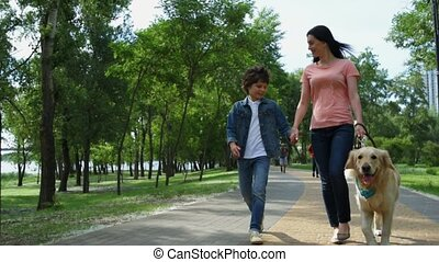 Mother and little son walking with a purebred dog