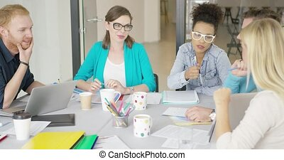 Young women and men working in office - Multiracial group of...