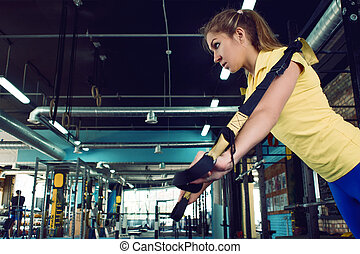 Young woman athlete trains using TRX, workout. On background...