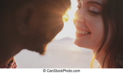 Couple kissing on sunset background - interracial couple...