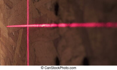 Construction laser level and red lines of a marking on a...