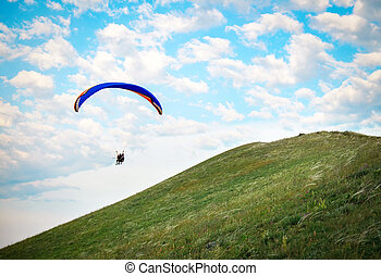 Trike with a parachute against the blue sky. Paragliding...