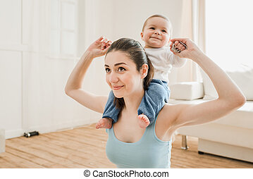 Portrait of young mother carrying her son piggyback at home