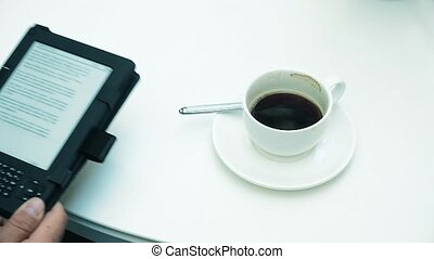 Young businessman reading news on tablet and drinking coffee in office 4k