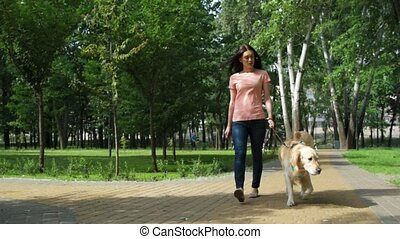 Joyful pretty woman walking with her dog - Have a nice rest....