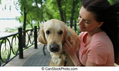 Loving young woman resting in the park with her dog - True...