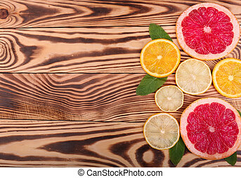 Fresh slices of juicy orange, ripe lemon, and organic grapefruit with leaves of mint on a wooden background, top view. A lot of citrus fruits on the right side.