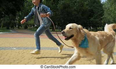 Overjoyed little boy running with his dog