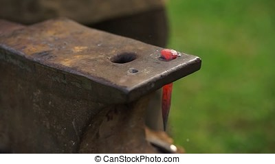 Smith forges a hot nail on the anvil - Blacksmith hammers...