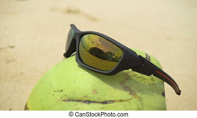 Sunglasses on coconut - Green coconut on the sand of a...