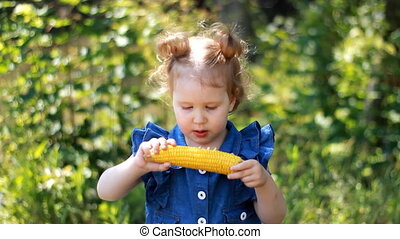 A little girl is eating corn. Picnic