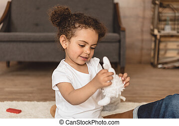 cute little kid girl playing with toy at home
