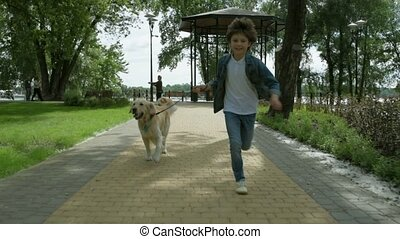 Cheerful little boy running with his dog