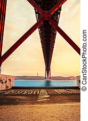 Sunset over the 25 de Abril bridge over Tagus river and...