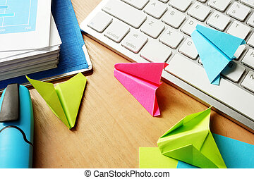 Procrastination concept. Colorful paper planes on an office...