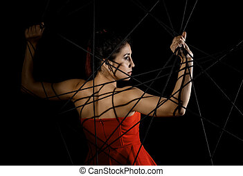 beautiful young woman in red dress entangled in a rope...