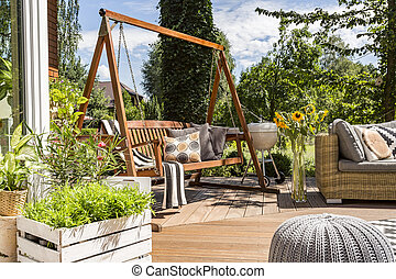 House patio with the garden swing - Shot of a wooden garden...