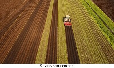 Tractor cultivates the land in the field. - Aerial view...