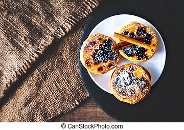 Delicious egg tart on a plate on wooden background with...
