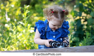 Funny curious baby girl is holding and photographing retro camera