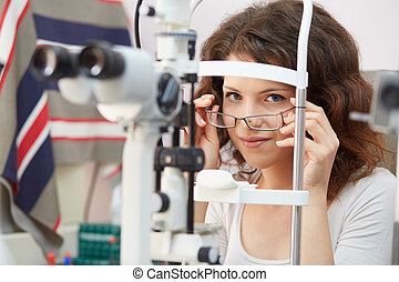pretty young woman having her eyes examined by an eye doctor