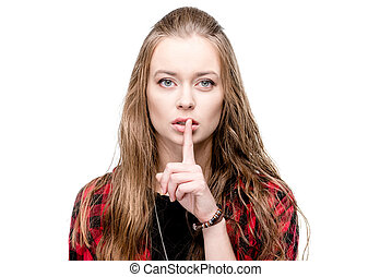 portrait of young attractive woman with silence gesture looking at camera isolated on white
