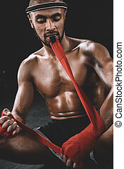 portrait of muay thai fighter swathing hand in boxing...