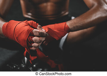 partial view of muay thai fighter swathign hand in boxing...