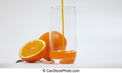 Slow motion of Orange juice pouring into clear glass shallow...