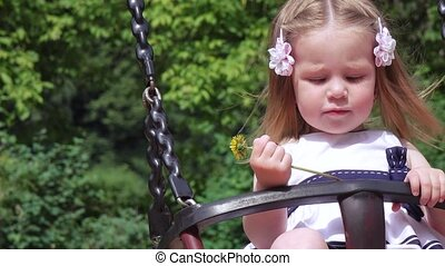 Girl riding on a swing mom - Girl riding a wooden horse on...